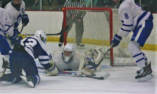 Catholic Central goalie Adam Blust covers up the puck during Saturday night's quarterfinal game against Salem.