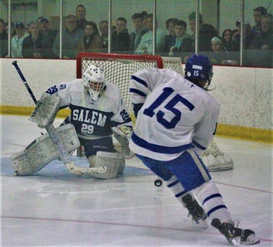 Catholic Central's Kyle Miller unleashes a shot at Salem goalie Andre Genereaux.