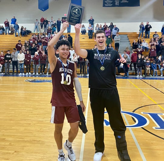 Matt Simmons and Patrick Murphy, captains of the New Paltz boys basketball team, raise the Section 9 Class A championship plaque after beating Monticello in the final on March 7.