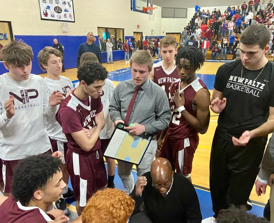 Coach Stu Robinson huddles his New Paltz High School boys basketball team in a timeout during the Section 9 Class A final on Saturday.