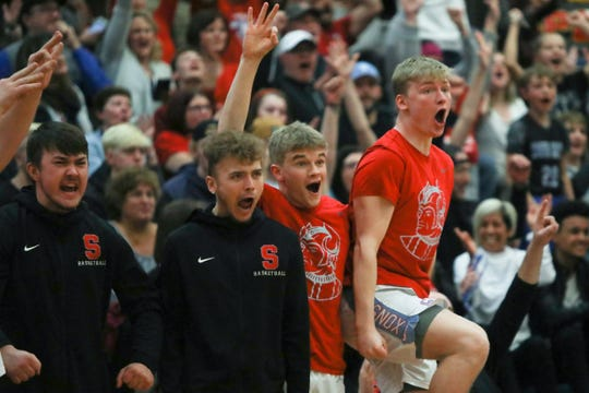 The South Salem bench celebrates a basket over Oregon City during the March 7 playoff game at South Salem High School.