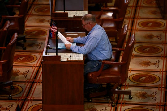 Senate Republican Leader Herman Baertschiger Jr., R-Grants Pass, reads a document from his desk on the Senate floor in the Oregon State Capitol Building in Salem, Oregon, on Sunday March 8, 2020.