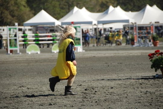 A young pony club member sprints out to fix a jump during the stadium jumping day at Red Hills Horse Trials 2020.