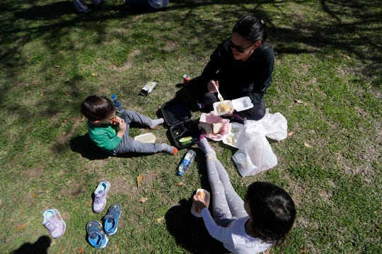 Lauren Overton and her kids Lyndon, 3, left, and Quinn, 4, enjoy their food in the grass during the Jewish Food Festival at Temple Israel Sunday, March 8, 2020.