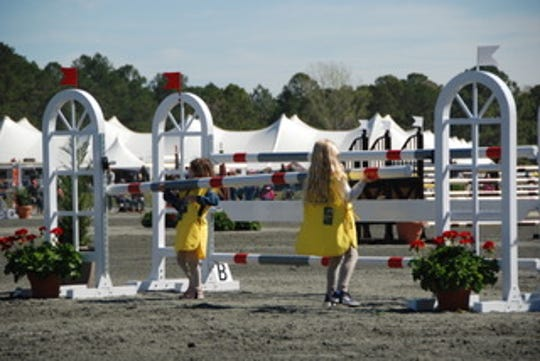 Young pony club members lift a rail back into place during the stadium jumping day at Red Hills Horse Trials 2020.