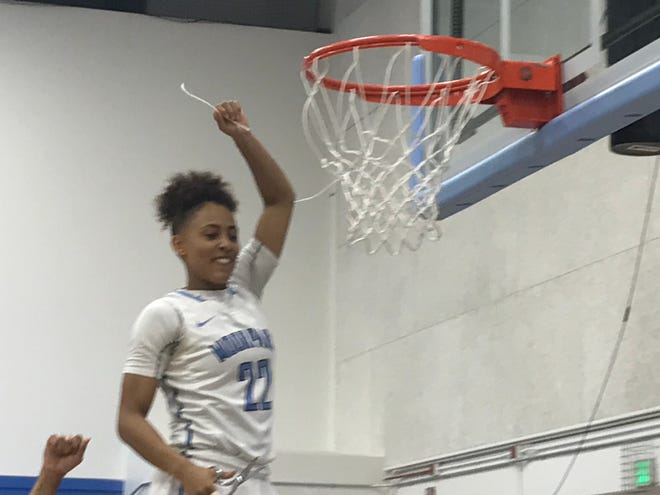 Moorpark College sophomore Bree Calhoun helps cut down the nets at Raider Pavilion after the top-seeded Raiders routed visiting Cypress, 70-39, in the CCCAA SoCal regional finals on Saturday night.