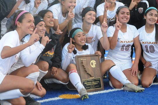 The Oxnard High girls soccer team poses with the championship plaque after beating host Chaminade High 2-1 in the CIF-State SoCal Division III regional championship on Saturday.