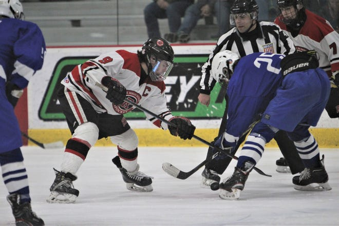 Rye forward Declan Lavelle (left) attempts to win possession of the puck during a faceoff against Whitesboro's Noah Scranton.