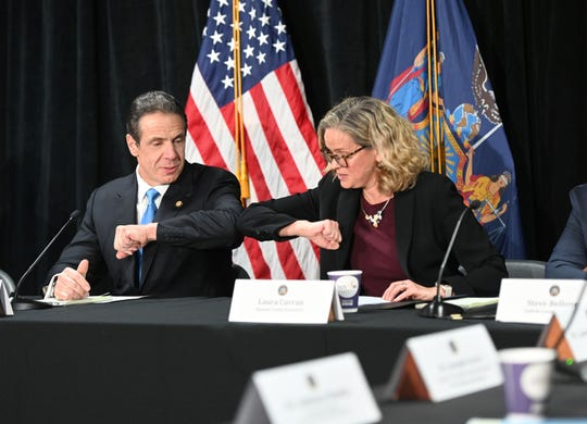 Instead of shaking hands, Gov.Andrew M. Cuomo bumps elbows with Nassau County Executive Laura Curran at a briefing on the novel coronavirus on Long Island  on March 5, 2020.