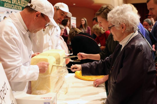 Catherine Lindsay, from Oshkosh, right, pulls a plug from a block of cheese at the March 5 reception at the World Championship Cheese Contest as cheese judge Kirk Baldwin, from South Dakota, left, watches.