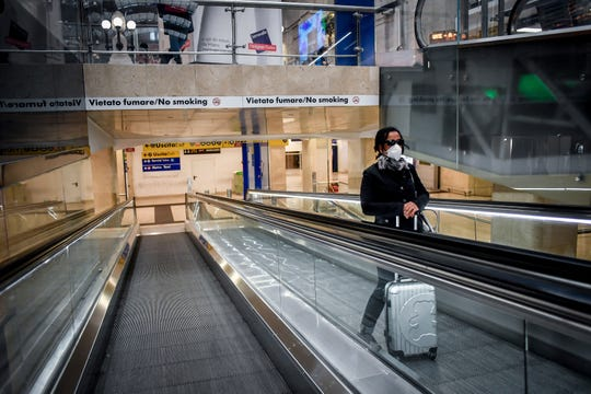 A woman wears a mask as she stands on an escalator inside Central train station, in Milan, Italy, Sunday, March 8, 2020. Italy announced a sweeping quarantine early Sunday for its northern regions, igniting travel chaos as it restricted the movements of a quarter of its population in a bid to halt the new coronavirus' relentless march across Europe.