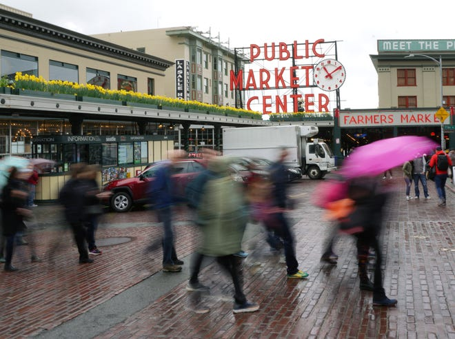 Tourists walk past the Public Market Center sign in downtown Seattle.