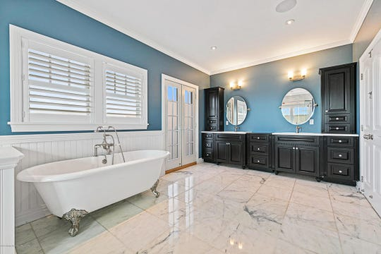 The master bathroom offers his and her customized sinks and marble flooring.