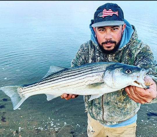 Matthew Calabria, Hazlet, with a catch and release of a striped bass on the Bay Shore on Raritan Bay.