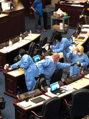 Cary Pigman, an ER doctor, helps House cleaning staff sanitize desks after five legislators and a staffer self-isolated because of possible exposure to coronavirus.