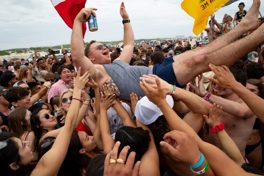 A man body surfs over a crowed of people as the celebrate spring break 2020 at the beach in Port Aransas on March 9, 2020.