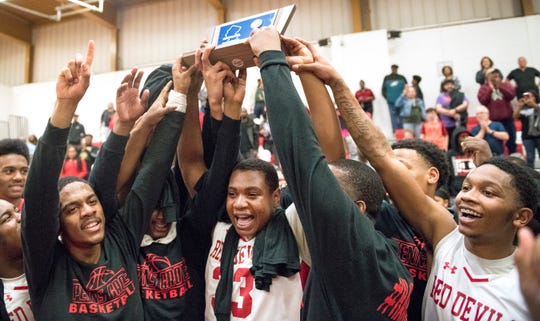 Members of the Penns Grove boys basketball team celebrate with their trophy after Penns Grove defeated Lindenwold, 68-51, in the South Jersey Group 1 boys basketball final played at Penns Grove High School on Monday, March 9, 2020.