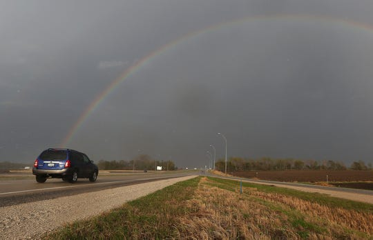 A car traveling eastbound on Highway 20 passes under a rainbow near Fort Dodge on May 8, 2014. Towns along U.S. Highway 20 could benefit from an effort that would place more than 100 historic markers along the entire 333 miles of the highway in Iowa.