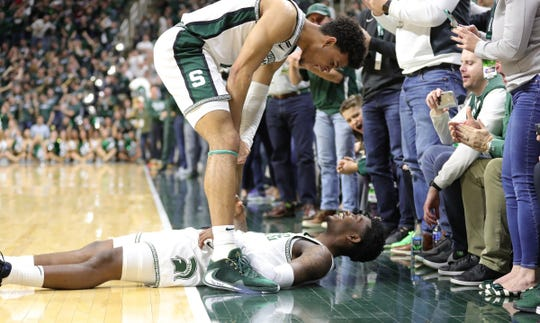 Michigan State's Rocket Watts lays on the ground in celebration with Malik Hall, after hitting a 3 during the 80-69 win against Ohio State on Sunday, March 8, 2020 at the Breslin Center.