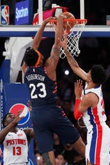 New York Knicks center Mitchell Robinson (23) dunks in front of Detroit Pistons forward Christian Wood (35) during the first half of an NBA basketball game in New York, Sunday, March 8, 2020. Detroit Pistons guard Khyri Thomas (13) watches, lower left. (AP Photo/Kathy Willens)
