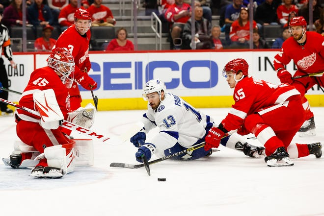 Tampa Bay Lightning center Cedric Paquette reaches for the puck as Detroit Red Wings goaltender Jonathan Bernier and left wing Dmytro Timashov (15) defend in March.