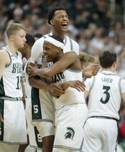 Michigan State guard Cassius Winston is met by forward Marcus Bingham Jr. as he leaves the court form the last time during MSU's 80-69 win over Ohio State on Sunday, March 8, 2020, at the Breslin Center.