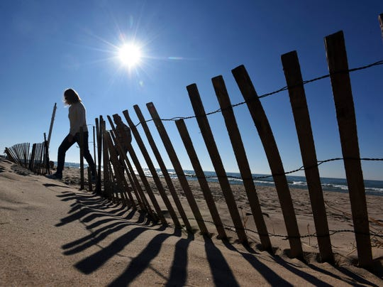 Beach walkers take advantage of clear weather Wednesday, March 4, 2020, as they stroll past snow fences at Silver Beach in St. Joseph, Mich.
