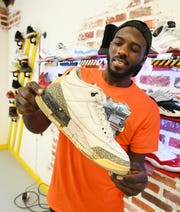 One of his most valuable pair of shoes, Frederick Paul shows off a pair of original 1991 Air Jordan 3's, despite some damage from use.
