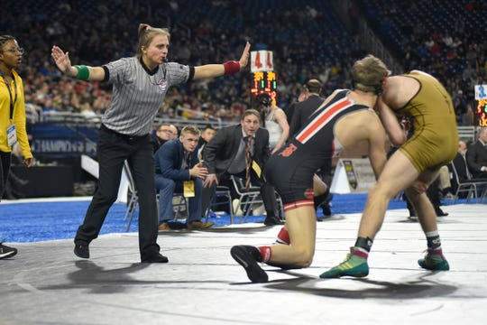 Cassandra Baranoski referees a match at the MHSAA individual wrestling championships Saturday at Ford Field in Detroit.