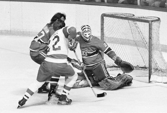 Canadiens goalie Ken Dryden, right, stops a shot by Red Wings forward Dennis Hextall as defenseman Rich Chartraw tries to help out at Olympia Stadium in 1978.