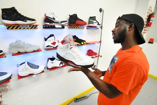 Fahrenheit 313 owner Frederick Paul pulls off the wall some Nike Air Jordan 5's in 'Fire Red.'
