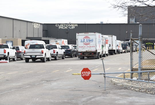 A long line of vehicles wait to enter Art Van's warehouse for customer pick-up in Warren on Monday.