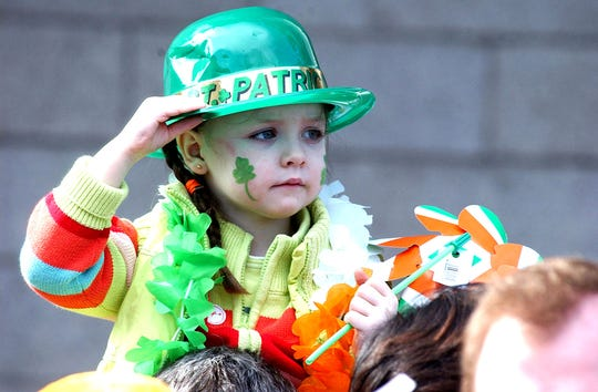 A young girl sits on an adult's shoulders while watching the St Patrick Day  parade in Dublin in this March 17, 2005, file photo. Irish authorities canceled the nation's annual St. Patrick's Day celebrations, as concern around the coronavirus outbreak escalated.