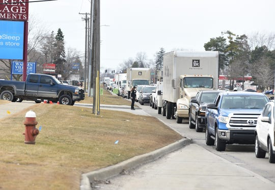 A long line of vehicles wait on eastbound 14 mile  to enter the Warren Art Van Furniture store on Warren on Monday afternoon.