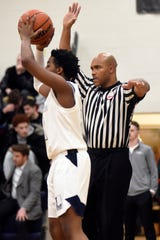 Basketball referee Myke Foster, right, officiates a boys basketball game between Detroit Loyola and U-D Jesuit last month at Bloomfield Hills Marian HIgh School.