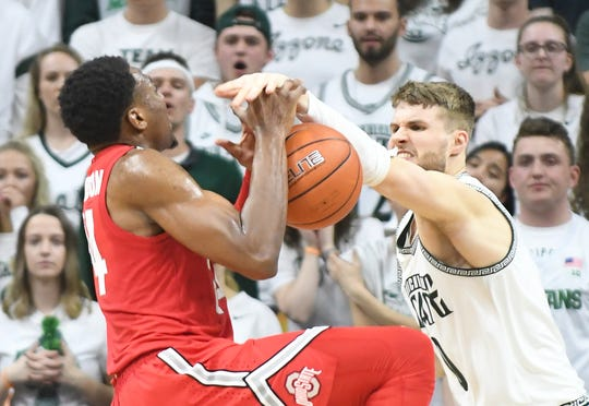 Ohio State's Andre Wesson gets the ball knocked away by Michigan State's Kyle Ahrens In the second half Sunday in East Lansing.