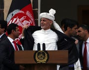 Afghan President Ashraf Ghani, center, opens his coat after a few rockets are fired during his speech after being sworn, at his inauguration ceremony at the presidential palace in Kabul, Afghanistan, Monday, March 9, 2020. To reassure his supporters, Ghani threw open his jacket saying he wasn't even wearing a bullet proof vest.