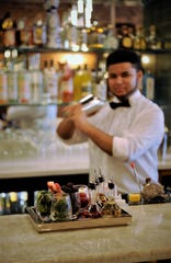Bartender Josiah Stewart shakes a cocktail at Entwined Wine & Dine on Thursday, Mar. 5, 2020.