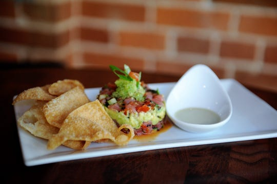 Tuna Tartare with avocado, cucumber, fresh tomato, wasabi tobiko and wasabi cream served with crisp wonton chips at Entwined Wine & Dine.