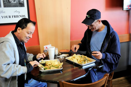John Reams, left, enjoys a Steak and Jalapeño Quesadilla while Patrick Tate samples a Southwest Chicken Quesadilla at Ghost Quesadilla in Newburgh on Saturday, Mar. 7, 2020.