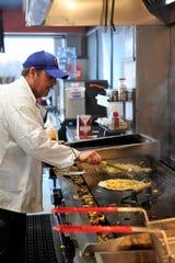Ryan London builds a Cheeseburger Quesadilla on a busy Saturday afternoon at Ghost Quesadilla on Saturday, Mar. 5, 2020.