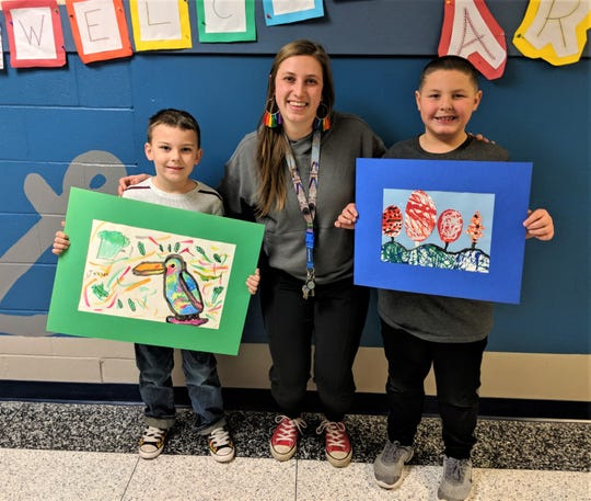 Bataan Memorial Primary student art work will be on display in Columbus, Ohio.  Pictured left to right:  Student artist Jackson Foos, grade one, Heather deHaas, Bataan Primary Art Teacher and  Gabriel Fick, grade one.