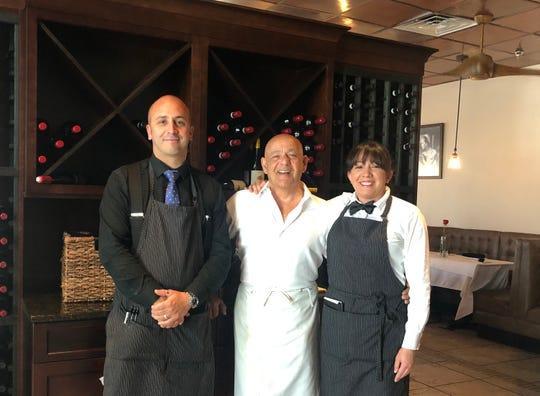 Ristorante Enrico's owner Enrico Costagliola, center, poses with his niece Ivana Rosa and his nephew Antonio Barone inside their Bonita Springs restaurant.