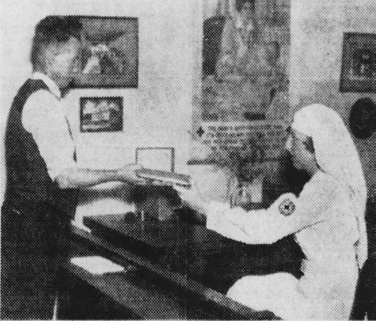 This photo from 1934 shows Belmont Kizziah, head of volunteer service, helping a former service man at the Red Cross headquarters then on West Washington Street.