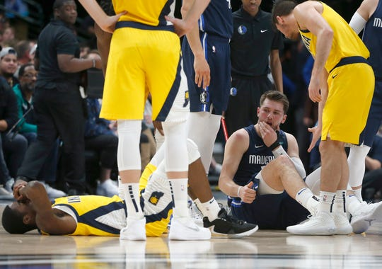 Dallas Mavericks guard Luka Doncic, second from right, reacts after being fouled by Indiana Pacers guard Edmond Sumner, left, during the first half of an NBA basketball game, Sunday, March 8, 2020, in Dallas.