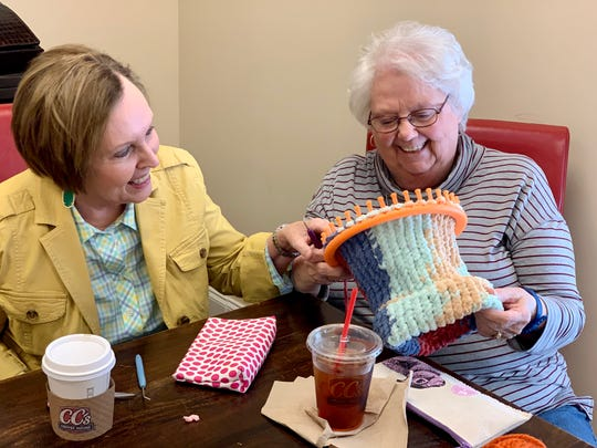 Olivia Redding of Madison, left, checks the progress of the hat that Marilyn Brantley of Madison knits.