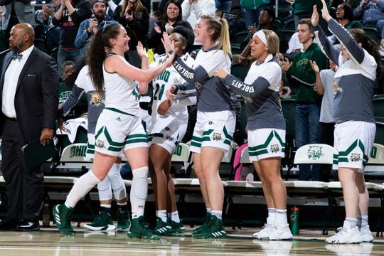 Gabby Burris is congratulated by her teammates after she scored her 1,000th career point Sunday against Miami University. Burris, a junior, is a former Liberty Union standout.