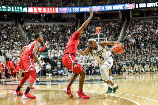 Michigan State's Cassius Winston, right, moves with the ball as Ohio State's Luther Muhammad defends during the second half on Sunday, March 8, 2020, at the Breslin Center in East Lansing.