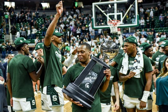 Cassius Winston holds the Big Ten championship trophy on Sunday. Winston and the Spartans are hoping for a long NCAA tournament run.