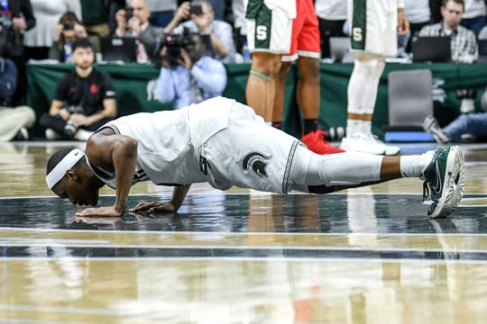 Michigan State's Cassius Winston kisses the floor before checking out during the second half on Sunday, March 8, 2020, at the Breslin Center in East Lansing.